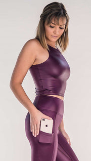 Side view of model wearing shiny eggplant purple sleeveless top