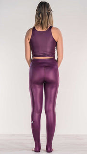 Rear view of model wearing shiny eggplant purple colored full length leggings with right side pocket