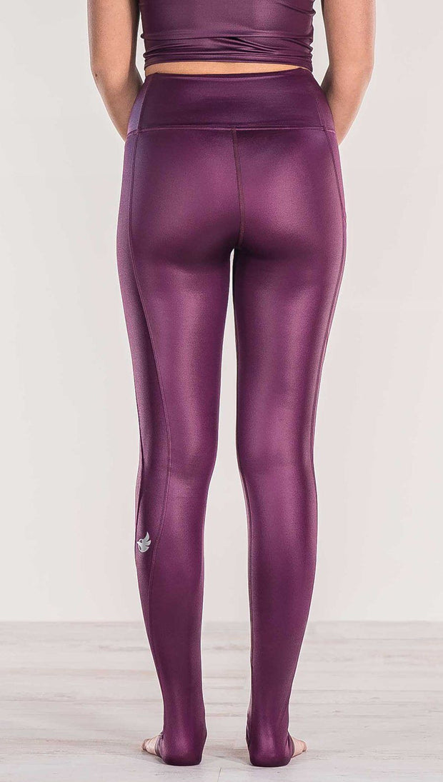 Close up rear view of model wearing shiny eggplant purple colored full length leggings with right side pocket