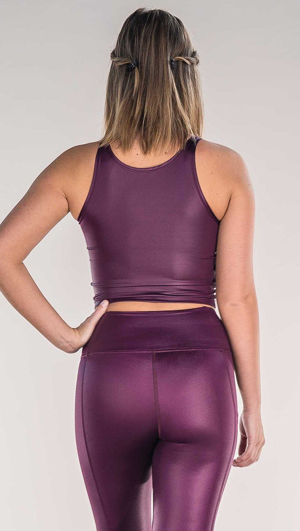 Back view of model wearing shiny eggplant purple sleeveless top