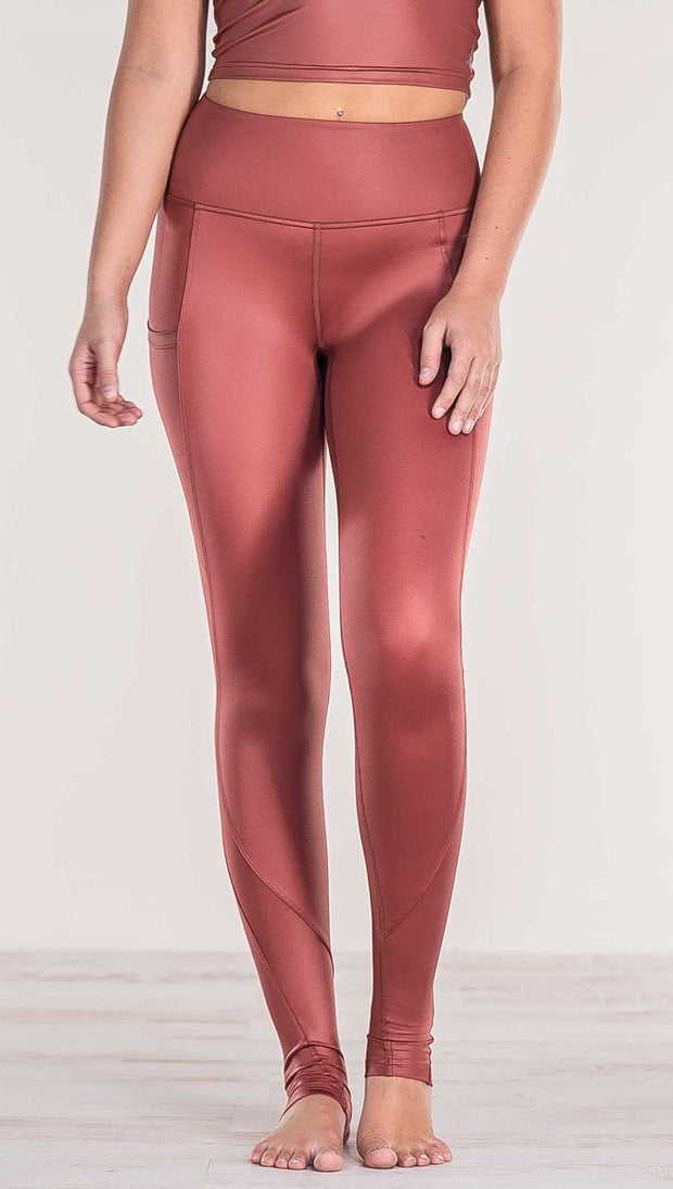 Close up front view of model wearing shiny mauve full length leggings with right side pocket