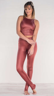 Front view of model crossing ankles wearing shiny mauve full length leggings with right side pocket