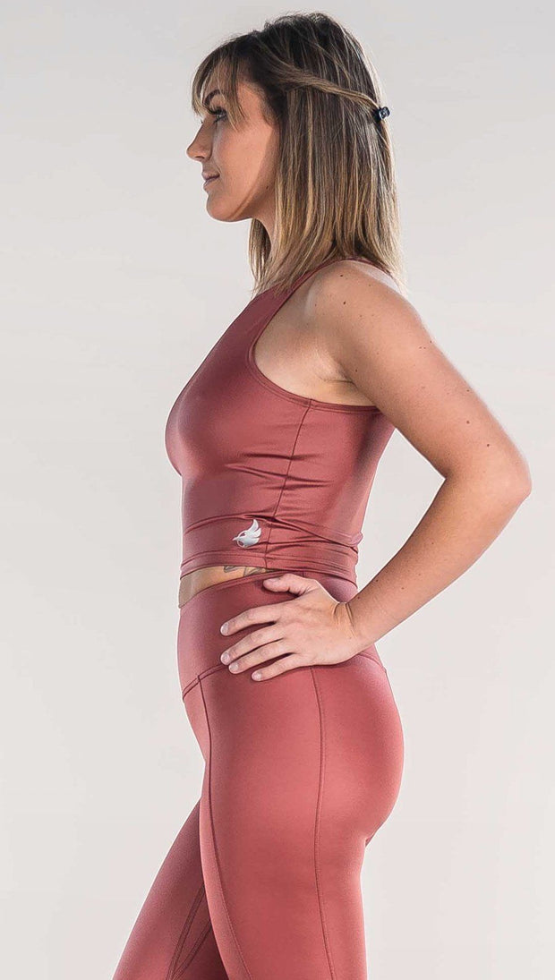 Side view of model wearing shiny mauve colored sleeveless top