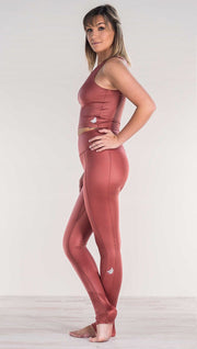 Side view of model wearing shiny mauve full length leggings with right side pocket