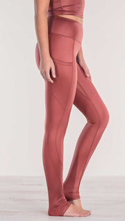Close up side view of model wearing shiny mauve full length leggings with right side pocket