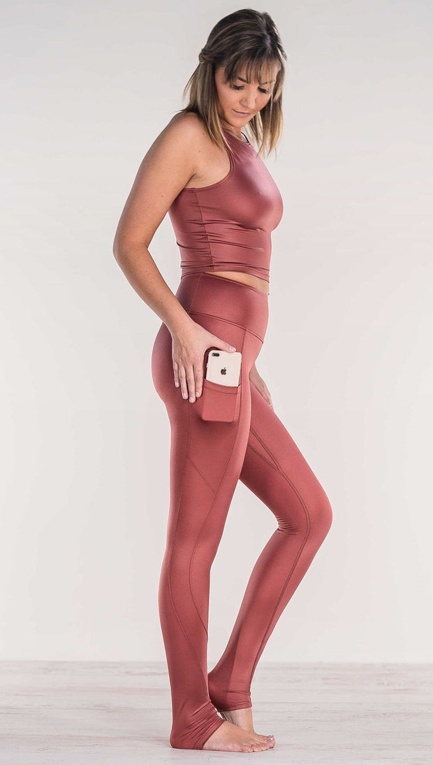 Side view of model wearing shiny mauve full length leggings putting iphone into right side pocket
