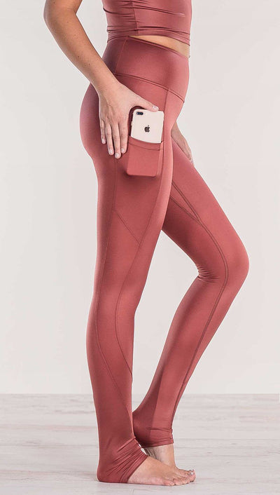 Close up side view of model wearing shiny mauve full length leggings putting iphone into right side pocket