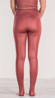 Close up rear view of model wearing shiny mauve full length leggings with right side pocket