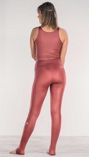 Rear view of model wearing shiny mauve full length leggings with right side pocket