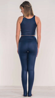 Rear view of model wearing shiny midnight blue full length leggings with right side pocket