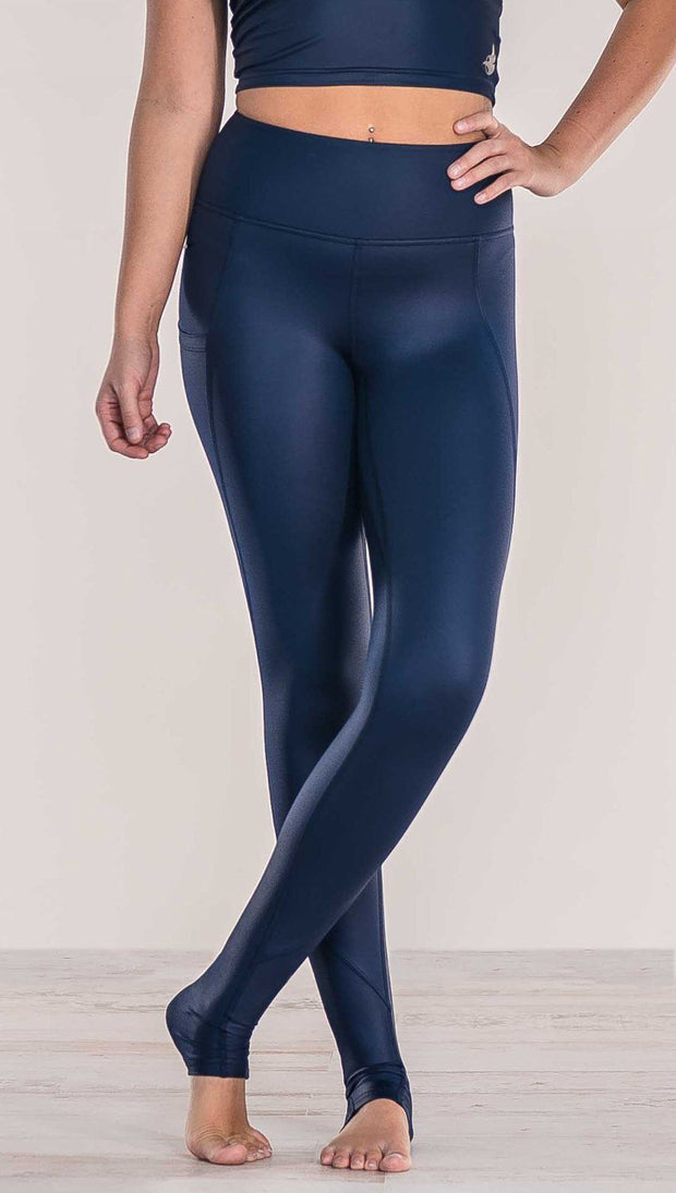 Close up front view of model crossing ankles wearing shiny midnight blue full length leggings with right side pocket