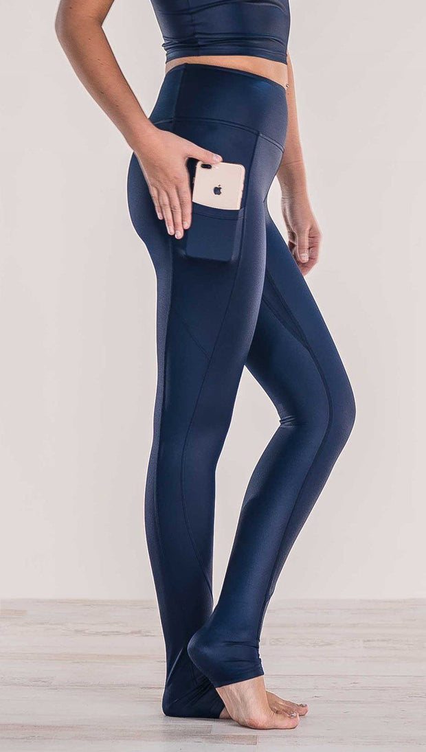 Close up side view of model wearing shiny midnight blue full length leggings putting iphone into right side pocket