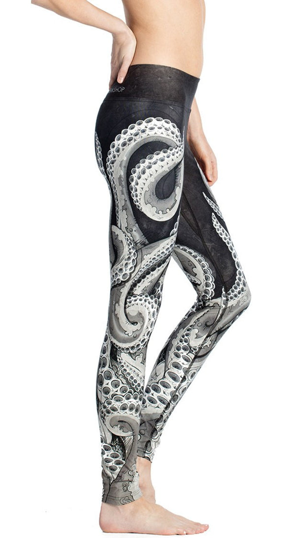 close up right side view of model wearing black and white tentacle themed printed full length leggings