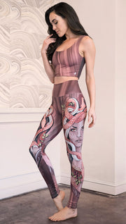 Slightly turned view of the model wearing full length athleisure leggings with a mauve color medusa head and red, white, and black snakes
