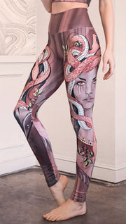 Left side view of the model wearing full length athleisure leggings with a mauve color medusa head and red, white, and black snakes