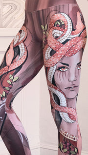 Zoomed in left side view of the model wearing full length leggings with a mauve color medusa head and red, white, and black snakes