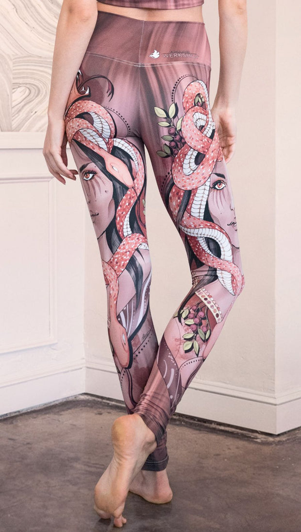 Zoomed in back view of the model wearing full length athleisure leggings with a mauve color medusa head and red, white, and black snakes