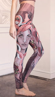 Right side view of the model wearing full length athleisure leggings with a mauve color medusa head and red, white, and black snakes