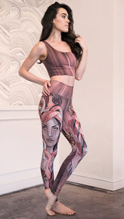 Slightly turned right side view of the model wearing full length athleisure leggings with a mauve color medusa head and red, white, and black snakes