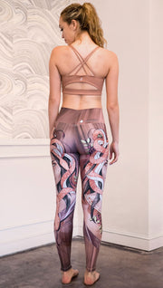 Back view of the model wearing full length athleisure leggings with a mauve color medusa head and red, white, and black snakes