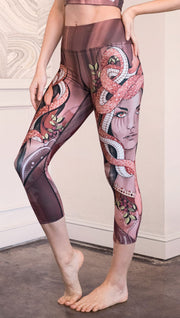 Left view of model wearing capri leggings with a mauve color medusa head and red, white, and black snakes