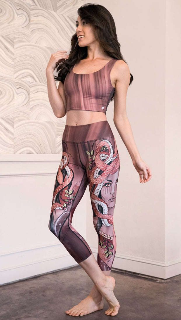 Zoomed out left view of model wearing capri leggings with a mauve color medusa head and red, white, and black snakes