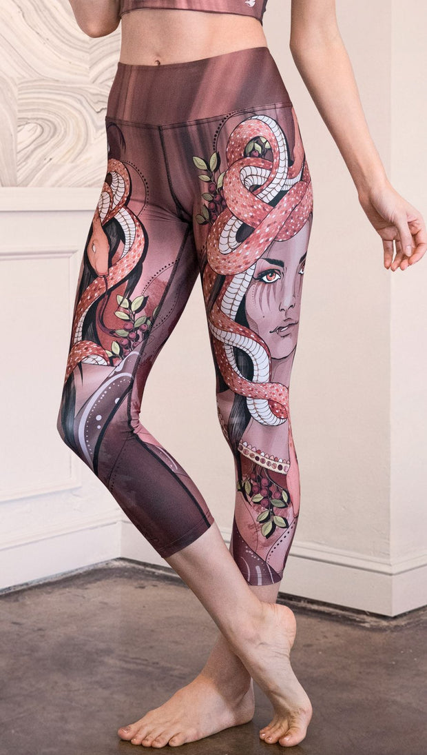 Model wearing capri leggings with a mauve color medusa head and red, white, and black snakes