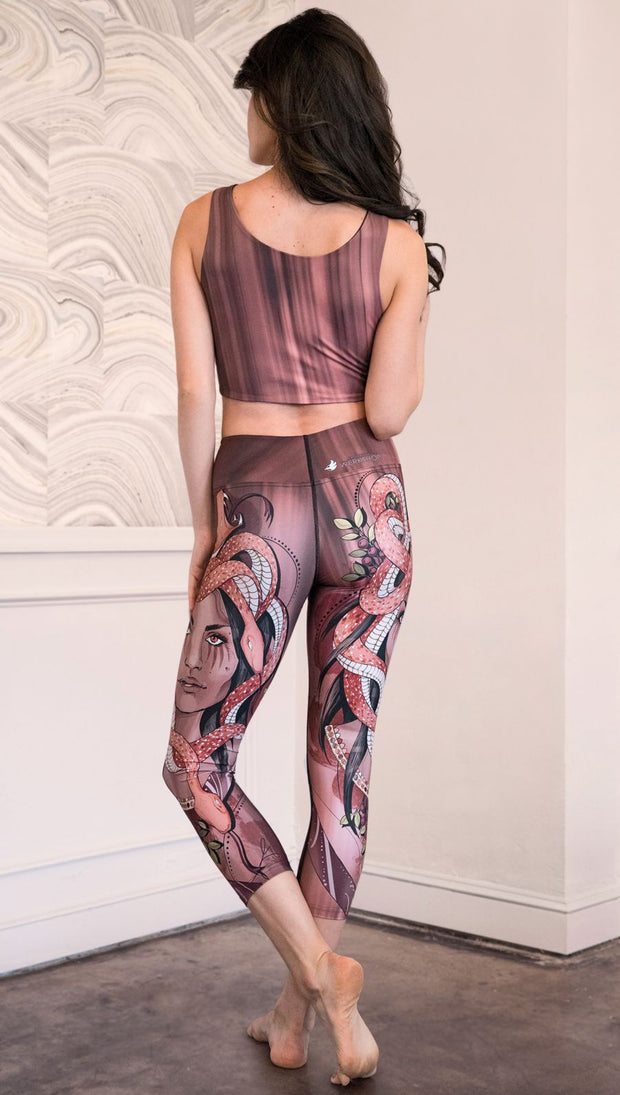 Back view of model wearing capri leggings with a mauve color medusa head and red, white, and black snakes