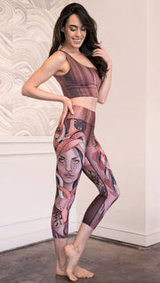 Right side view of model wearing capri leggings with a mauve color medusa head and red, white, and black snakes