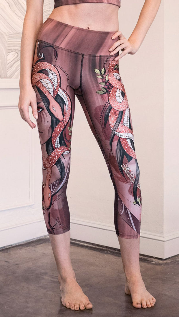 Zoomed in front view of model wearing capri leggings with a mauve color medusa head and red, white, and black snakes