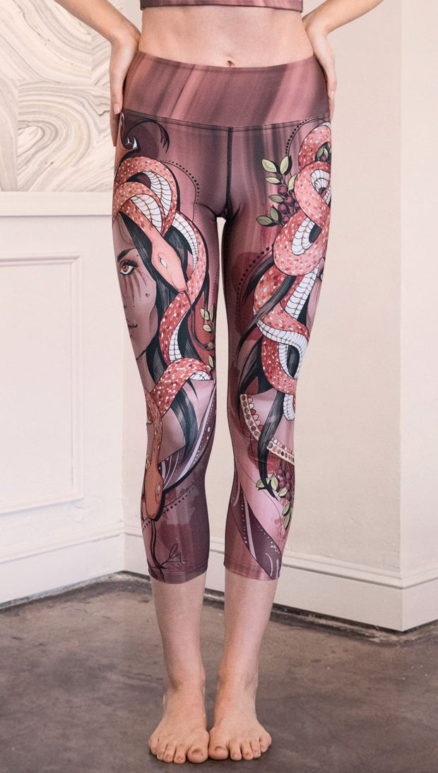 Front view of model wearing capri leggings with a mauve color medusa head and red, white, and black snakes