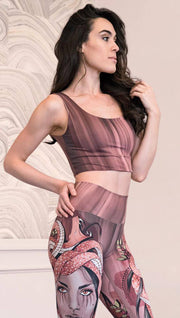 Right side view of model wearing a mauve color sleeveless crop top with black brushstrokes