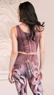 Back view of model wearing a mauve color sleeveless crop top with black brushstrokes