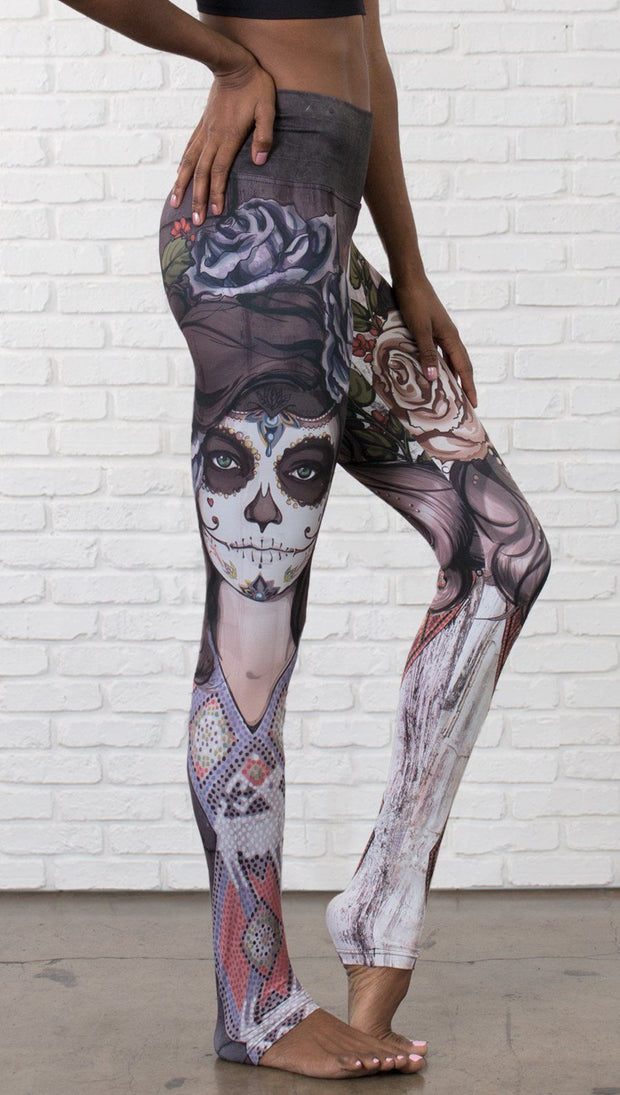 closeup right side view of model wearing mashup Sugar Skull and Dia De Los Muertos themed printed full length leggings