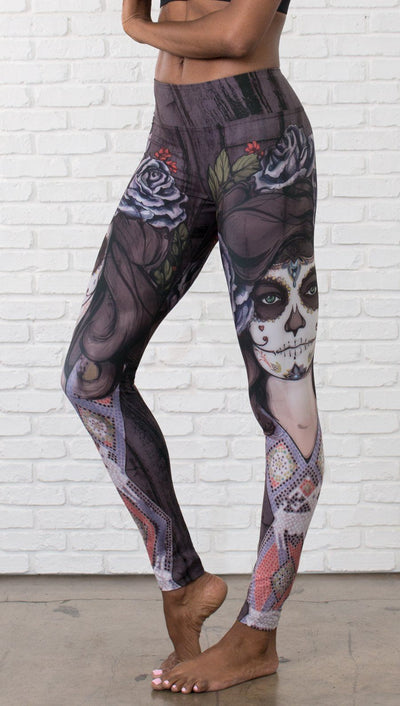 close up left side view of model wearing sugar skull themed printed full length leggings
