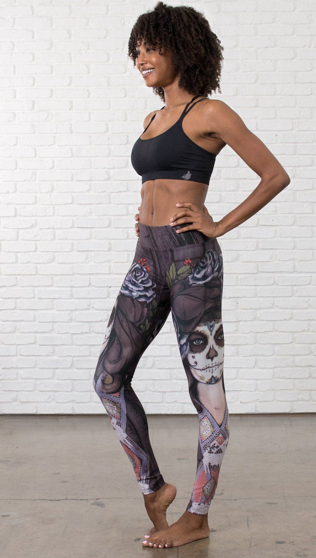 slightly turned front view of model wearing sugar skull themed printed full length leggings