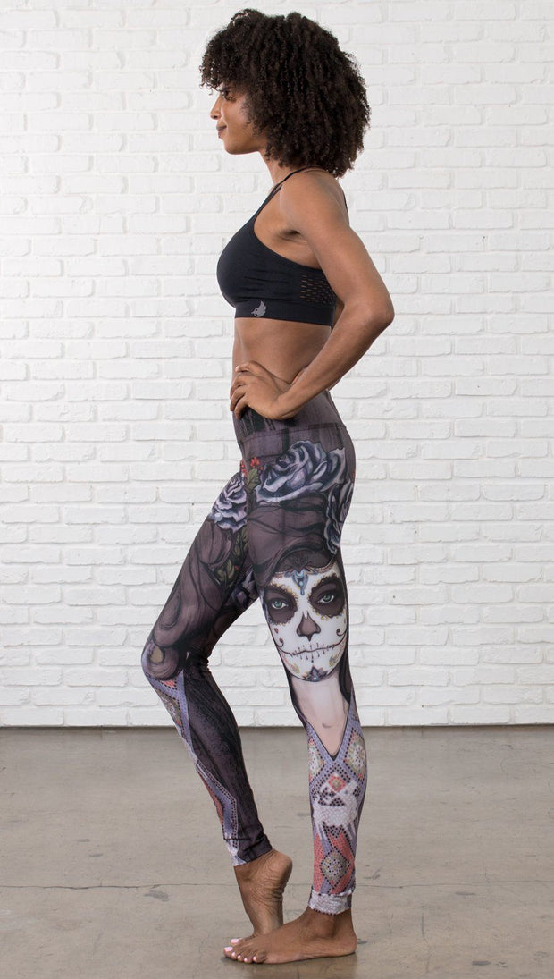 left side view of model wearing sugar skull themed printed full length leggings