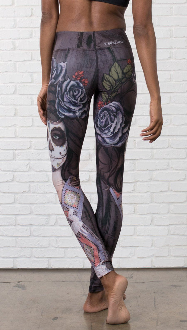 close up back view of model wearing sugar skull themed printed full length leggings