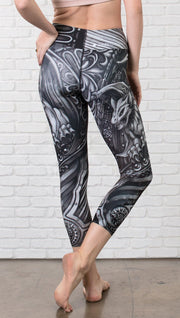 back view of model wearing gothic themed printed capri leggings