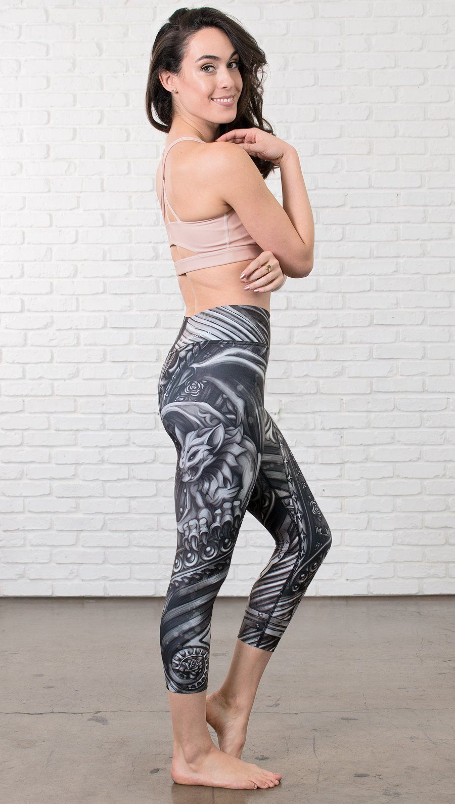 closeup left side view of model wearing gothic themed printed capri leggings
