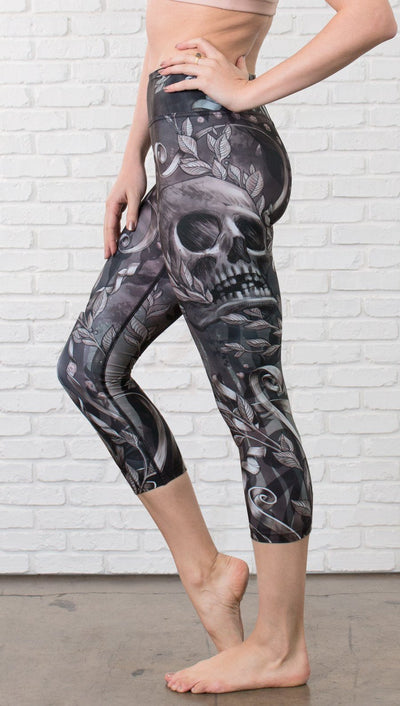 close up left side view of model wearing gothic themed printed capri leggings
