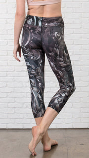 close up back view of model wearing gothic themed printed capri leggings