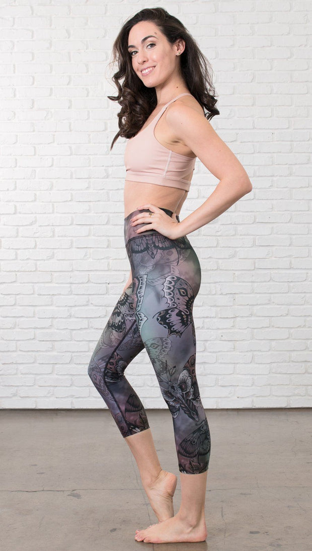 left side view of model wearing capri printed leggings with gothic moths, gargoyles, skulls, ravens design