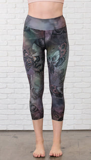 closeup front view of model wearing capri printed leggings with gothic moths, gargoyles, skulls, ravens design