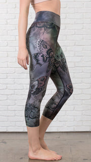closeup right side view of model wearing capri printed leggings with gothic moths, gargoyles, skulls, ravens design