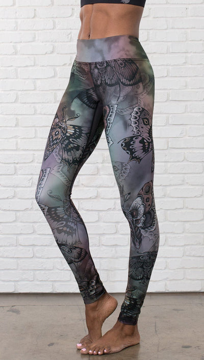 closeup front view of model wearing full length printed leggings with gothic moths, gargoyles, skulls, ravens design