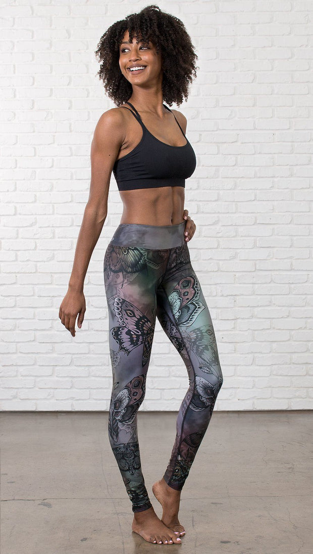 right side view of model wearing full length printed leggings with gothic moths, gargoyles, skulls, ravens design