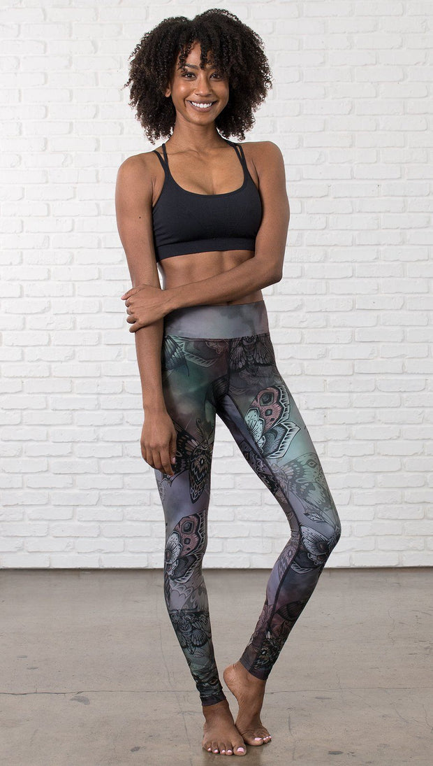 front view of model wearing full length printed leggings with gothic moths, gargoyles, skulls, ravens design