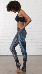 left side view of model wearing gothic themed printed full length leggings