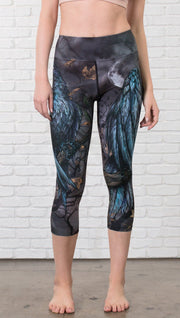 closeup front view of model wearing gothic themed printed capri leggings